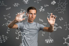 Man scientist in white shirt working with chemical formulas on gray background. Royalty Free Stock Photos