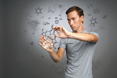 Man scientist in white shirt working with chemical formulas on gray background. Royalty Free Stock Photography