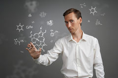 Man scientist in white shirt working with chemical formulas on gray background. Stock Images