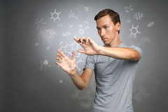 Man scientist in white shirt working with chemical formulas on gray background. Young man scientist in white shirt working with chemical formulas on gray Stock Photo