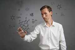 Man scientist in white shirt working with chemical formulas on gray background. Royalty Free Stock Images