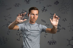 Man scientist working with chemical formulas on gray background. Young man scientist working with chemical formulas on gray background Royalty Free Stock Photos