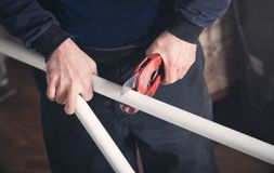 Man with scissors cutting plastic pipe royalty free stock images