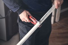 Man with scissors cutting plastic pipe stock photo