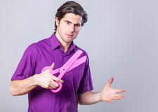 Man with scissors. Man with huge scissors on gray background Stock Photos