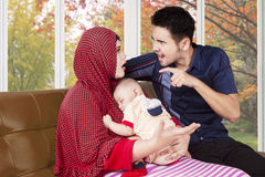 Man scolding his wife while holding baby. Portrait of young men scolding his wife at home while holding a baby, shot with autumn background on the window Stock Image