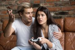 Man scolding woman for losing playing video game at home. Angry men scolding nervous young women for losing videogame, worried girl playing video game at home Royalty Free Stock Photos