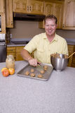 Man scooping cookies Royalty Free Stock Photos