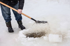 Man scoops chunks ice out of the hole Royalty Free Stock Images