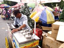 A man scoops up ice cream from his cart Royalty Free Stock Photos