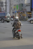 Man with scooter. In a downtown intersection Royalty Free Stock Image
