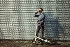 Man with scooter drinking coffee against the background of the modern building stock photos