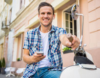 Man on scooter. Handsome young man is sitting on scooter with smartphone and listening music Stock Images