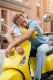 Man on scooter is sleeping. Stock Photo