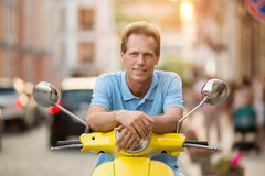 Man on scooter is smiling. Stock Image
