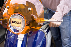 Man with scooter with 'sold' sign, close-up Royalty Free Stock Image