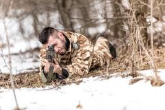 Man with scoped rifle. A man with camouflage outfit and scoped rifle lying on the ground and looking through the scope Royalty Free Stock Photos