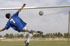 Man Scoring Goal During Soccer Match. Rear view of young man scoring goal during soccer match Stock Image