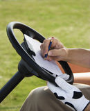 Man Scoring Golf. Male golfer writing his golf score while sitting in a golf cart. Vertical shot Stock Photography