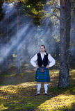 Man in scottish costume in the forest Stock Photo