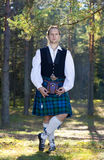 Man in scottish costume in the forest Stock Images