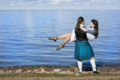 Man in scottish costume holding woman Stock Photos