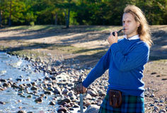 Man in scottish costume with pipe Royalty Free Stock Image