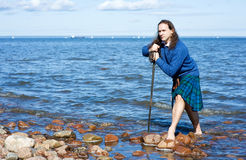 Man in scottish costume in the water Stock Photography