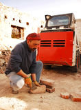 Man Scraping Bricks in Front of Bobcat Skid Loader. A man scrapes excess cement from antique bricks being salvaged for further architectural use from the Royalty Free Stock Photography