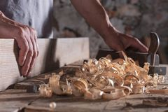 Man scraping curled wood scraps with hand plane tool. Carpenter man scraping curled wood scraps with hand plane tool and wooden plank. Blurry stone wall in stock photography