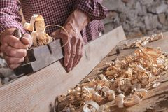 Man scraping curled wood scraps with hand plane tool. Carpenter man scraping curled wood scraps with hand plane tool and wooden plank. Blurry stone wall in royalty free stock images