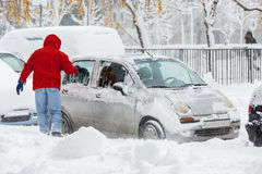 Man scraping frozen snow from the car windows Stock Images
