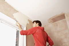 Man Scraping Paint Off Wall In Unrenovated Room Royalty Free Stock Images