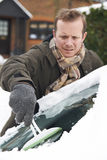 Man Scraping Snow From Car Windscreen Royalty Free Stock Image