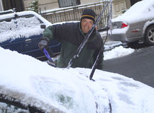 Man scraping snow from windshield Royalty Free Stock Photos