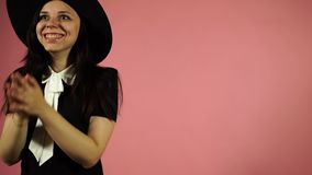 Lady smiling on a pink background. Woman pleasantly surprised stock video