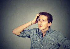 Man scratching head, thinking about something, looking up Stock Images