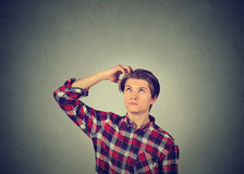 Man scratching head, thinking about something, looking up Royalty Free Stock Image