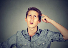 Man scratching head, thinking about something, looking up Royalty Free Stock Photos