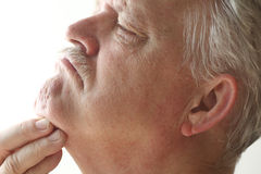 Man scratching under his chin. Older man has irritation on the skin under his chin Stock Photo