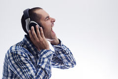 Man scream with headphones. On his ears, wearing a plaid shirt Stock Photos