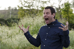 Man screaming in anger with hands out and mouth wide open. Royalty Free Stock Images