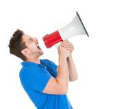 Man screaming into bullhorn while pointing away Stock Photo