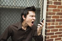 Man screaming at cell phone. Royalty Free Stock Photography