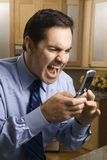 Man screaming at cellphone. Mid-adult Caucasian male screaming at cell phone while standing in kitchen Royalty Free Stock Photography
