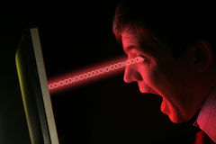 Man screaming at data transfer. A man in shirt and tie screams at a red computer monitor data streams into his eyes Royalty Free Stock Image