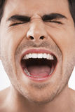 Man Screaming With Eyes Closed. Closeup of young man screaming with eyes closed on white background royalty free stock photography