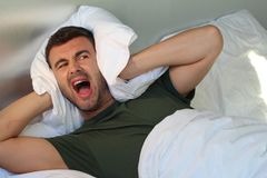 Man screaming at home while covering ears stock images