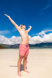 Man screaming of joy with hands up on the beach. Young naked man screaming of joy with hands in the air on the beach Royalty Free Stock Photography