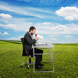 Man screaming with megaphone at outdoor. Angry businessman screaming with megaphone and looking at laptop. photo at outdoor Stock Photo